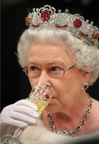 Queen Elizabeth wearing a diamond and ruby tiara while drinking Champagne