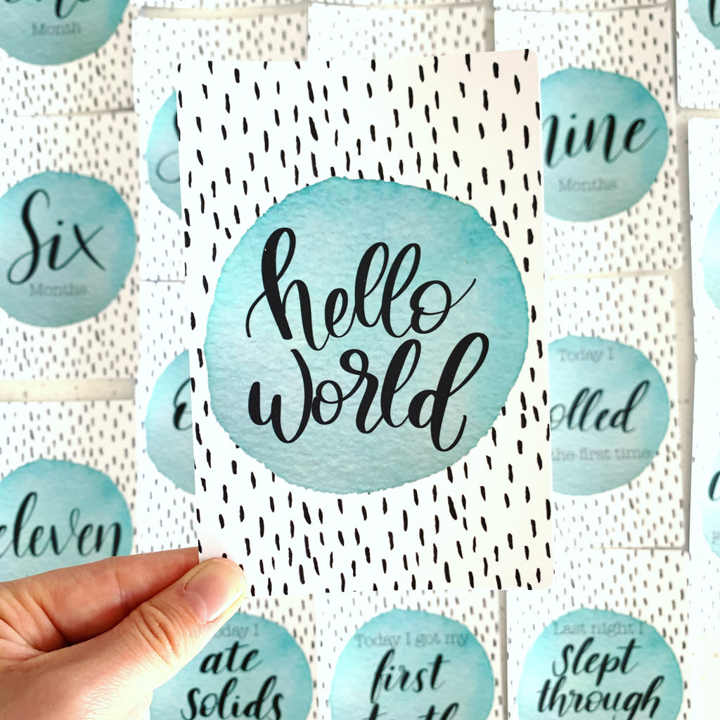 hand holding baby milestone card. Hello World