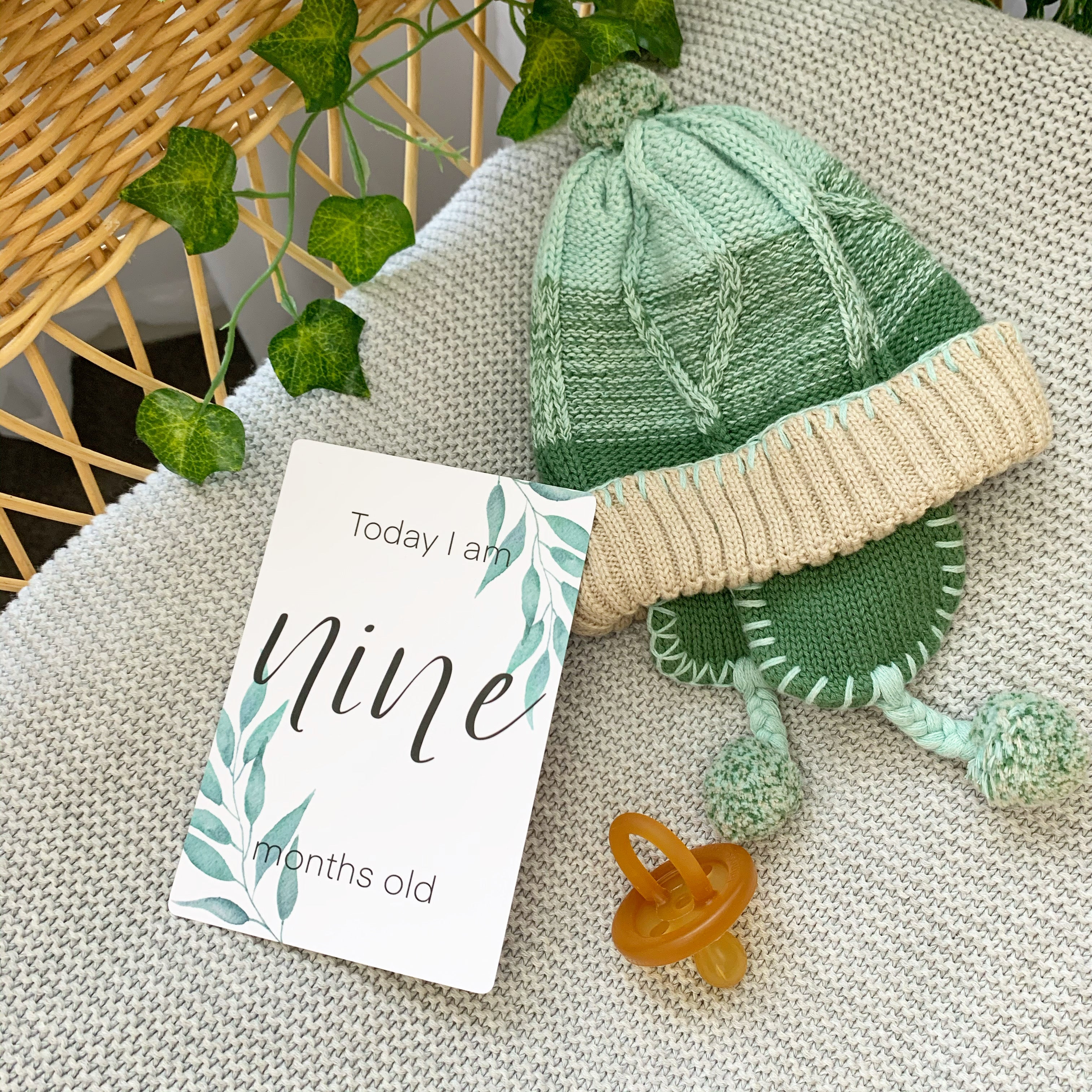 leaf milestone card in cane bassinet with leaves, green knitted baby bonnet/beanie, natural rubber soother/dummy
