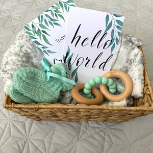 hello world leaf baby milestone card in gift basket with aqua baby booties, baby teether and swaddle