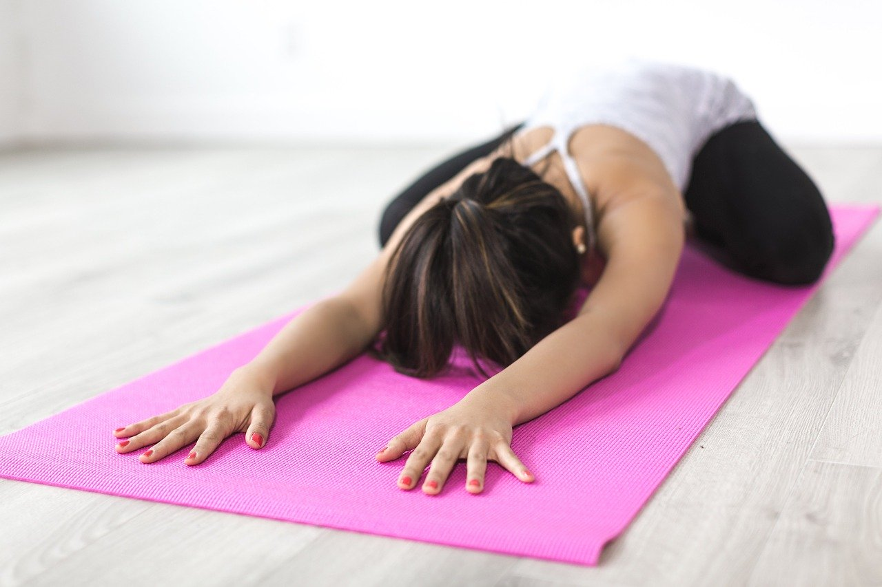 fit woman stretching on pink yoga mat at home.