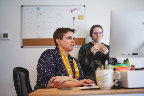 two people looking at a computer; on the left a woman with short brown hair wearing a yellow scarf. On the right a person in a beanie eating a peanut butter sandwich