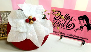 Small circle fascinator of red satin, with white poinsettia and gold and green trim.