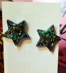 Star shaped resin earrings with pink and teal glitter flecks. Stainless steel posts.