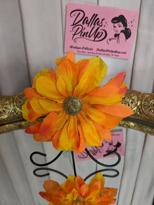 Handmade by local designer, Dream Hats. Vibrant orange and yellow hair flower with ornate gold center and metal clip attachment