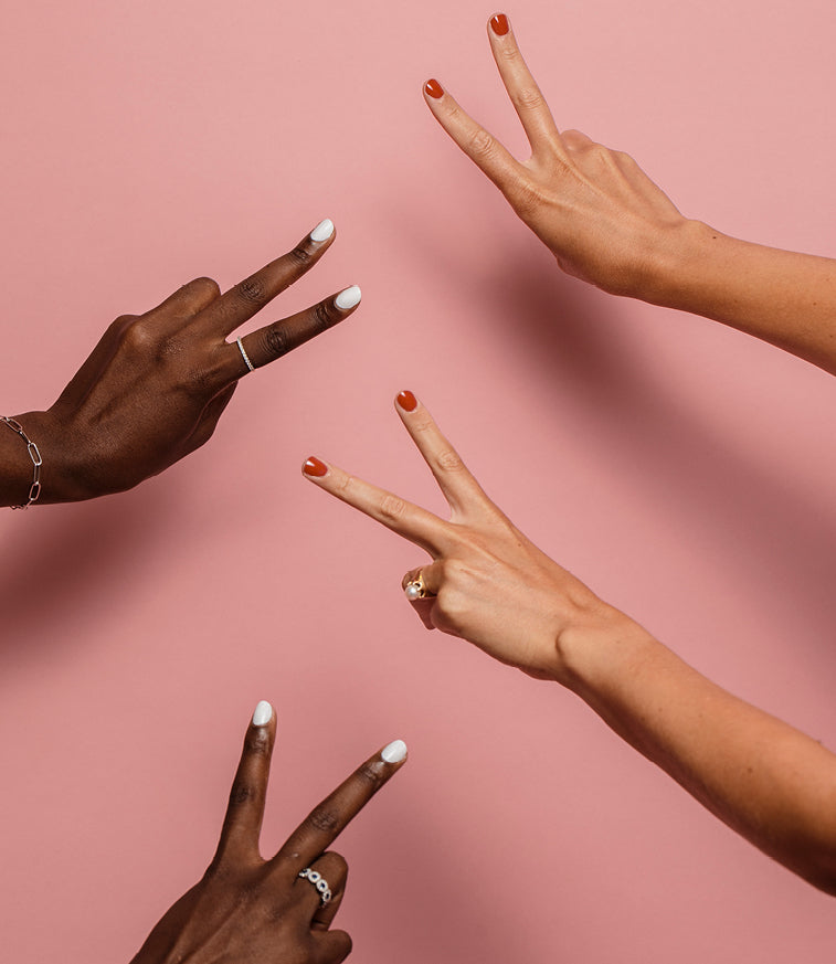 Two sets of female hands in peace sign positions with white and red manicures
