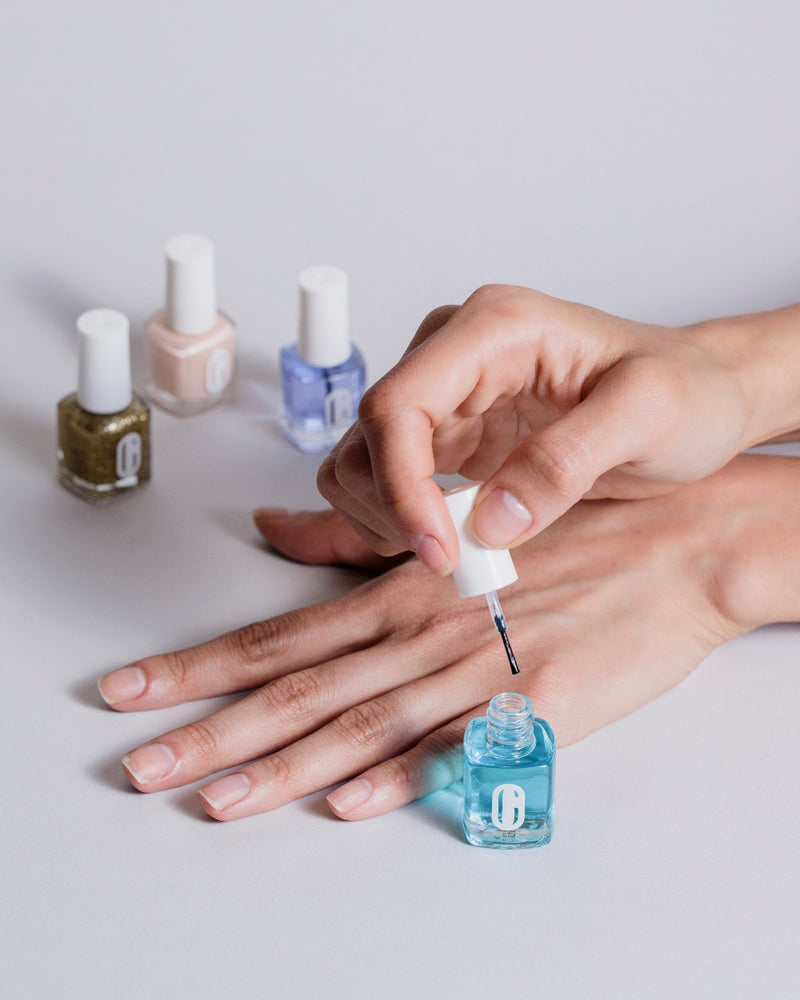 Image of female applying clear gel polish to nail with other nail polish colors in background