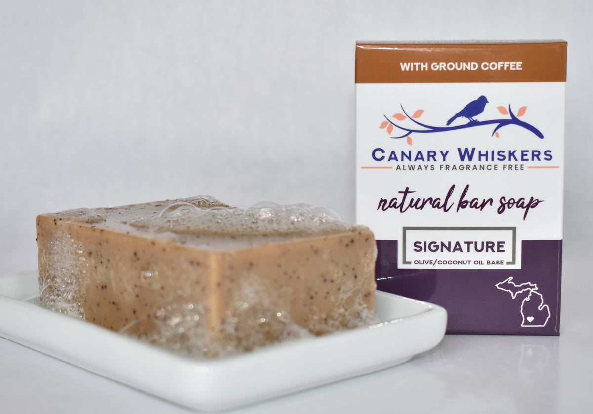 Bar of coffee fragrance-free soap with bubbles on a soap dish next to a boxed coffee soap package.