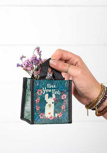 Natural Life recycled gift bag 3.5 in square dark teal bag with white llama surround by wreath of pink flowers.  Text says Llove you llots. Small webbed handles