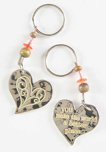 bright silver 2 sided keychain in a whimsical heart shape  Side 1 is  stamped with a white scrolly heart shape and side 2 has text 'you make the world a better place''