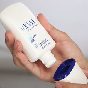 Woman holding Obagi Nu-Derm BlendFx by hoodermatology.com