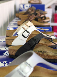 A collection of Birkenstock shoes on display in seveal colours