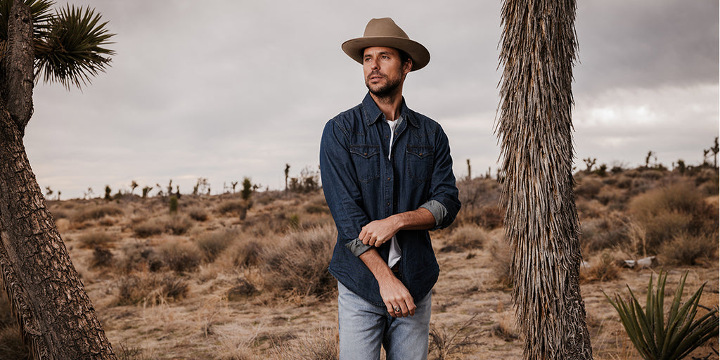 Stetson Denim Shirt - A Man Wearing a Denim Shirt in the desert with a hat on rolling up his sleeves