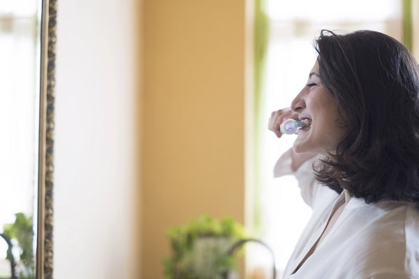 A woman brushing her teeth with the ION-Sei toothbrush