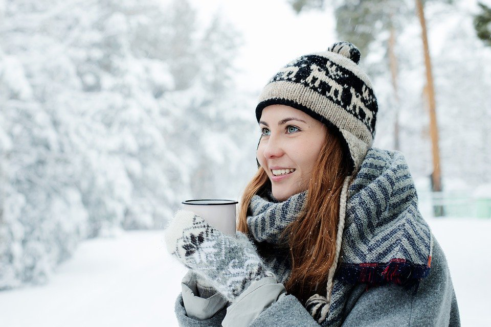 An image of a girl with pearly white teeth standing outdoors in the snow.