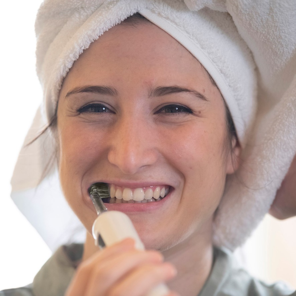 A woman brushing her teeth with the ION-Sei toothbrush to remove tartar