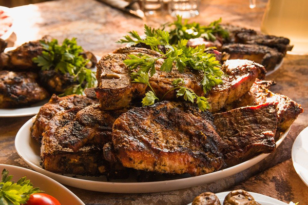 a plate full of beef steak and garnished with herbs
