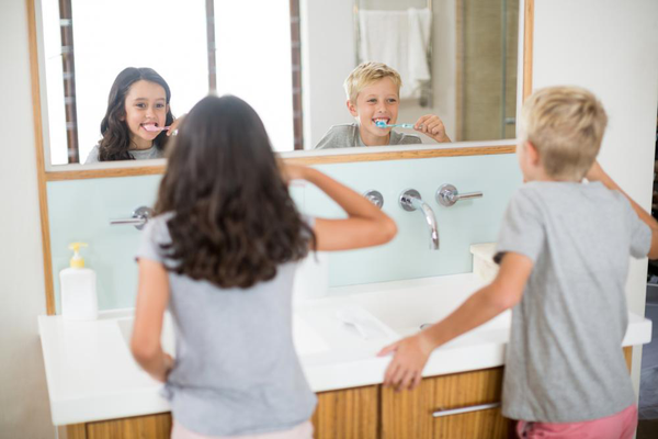 Siblings brush teeth in the bathroom