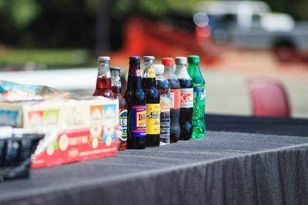 An image of different carbonated beverages and sugary drinks sitting on a table.