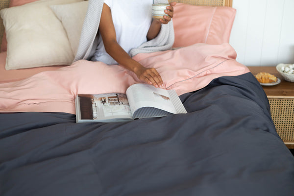 the picture is of a young women sitting in bed with a cup of tea reading a magazine in the bamboo cotton sheets