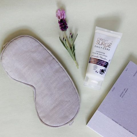 Organic Surge Comforting Hand and Nail cream placed on parchment paper next to a sleep mask, a cutting of lavender and a sleep diary.