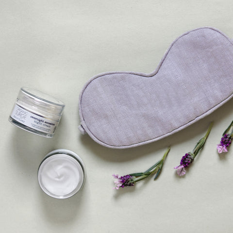 Organic Surge Overnight Sensation cream rests between a sleep mask and three lavender cuttings.