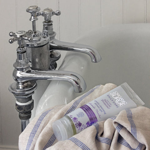 Organic Surge Gently Cleansing Shower Gel sits on the edge of a bath in a white, brightly lit bathroom wrapped in a towel