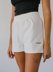 woman in white high-waisted shorts with float logo