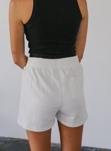 woman in white high-waisted shorts with small patch pocket