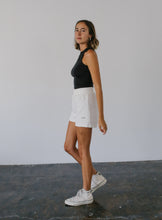 Load image into Gallery viewer, woman in white high-waisted shorts with float logo