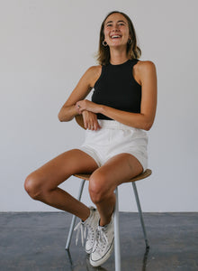 woman in white high-waisted shorts with float logo sitting on a chair