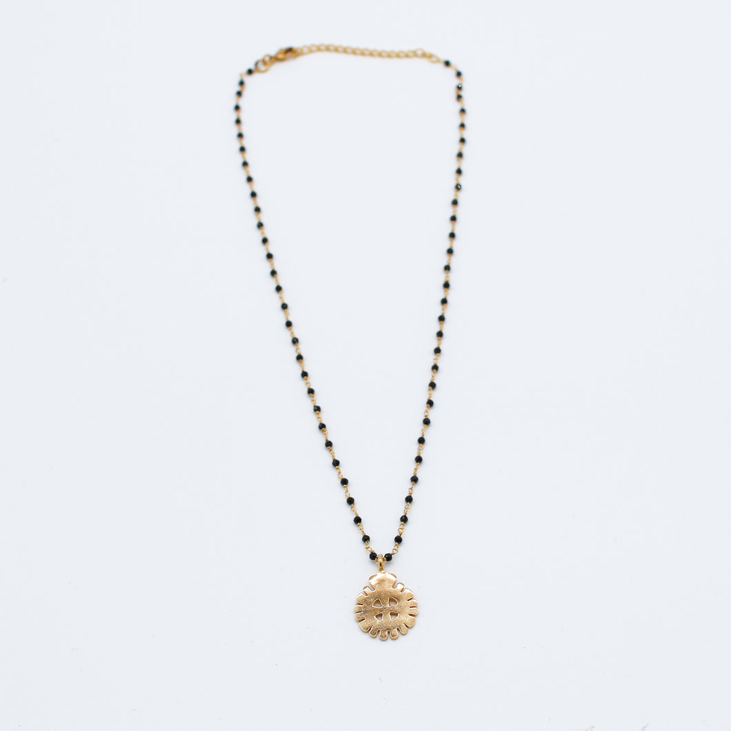 Gold chain with black beads and a gold circular pendant
