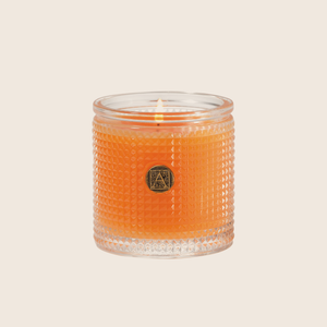 The Valencia Orange Textured Glass Candle transforms a room with the fragrance of sweet oranges mixed with notes of apples and red berries with a hint of citrus peel. Our candles are all hand-poured in Arkansas. Made with a proprietary wax blend, ethically sourced containers and cotton wicks. Light one of these aromatic candles and transport yourself to a memory or emotion.