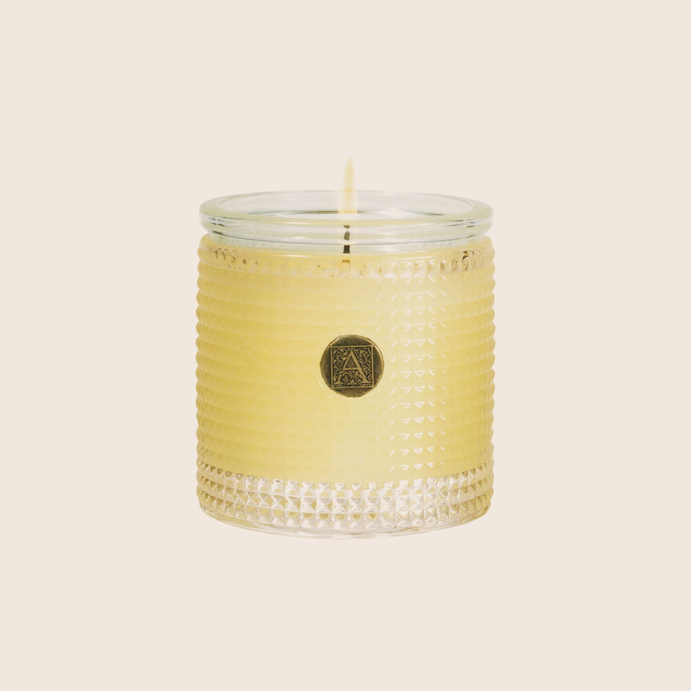 The Orange & Evergreen Textured Glass Candle evokes a wintery scene; fragrant citrus fruits with a touch of evergreen, cardamom and florals. Our candles are all hand-poured in Arkansas. Made with a proprietary wax blend, ethically sourced containers and cotton wicks. Light one of these aromatic candles and transport yourself to a memory or emotion.