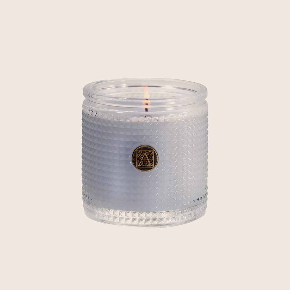 The Viola Driftwood Textured Glass Candle conjures an oceanside scene with a calm, watery fragrance of violet leaves paired with cedar, vetiver, and infused citrus. Our candles are all hand-poured in Arkansas. Made with a proprietary wax blend, ethically sourced containers and cotton wicks. Light one of these aromatic candles and transport yourself to a memory or emotion.