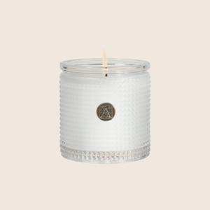 The White Teak & Moss Textured Glass Candle is the perfect everyday scent with a clean fragrance of fresh citrus over notes of earthy moss, coconut, and sandalwood. Our candles are all hand-poured in Arkansas. Made with a proprietary wax blend, ethically sourced containers and cotton wicks. Light one of these aromatic candles and transport yourself to a memory or emotion.