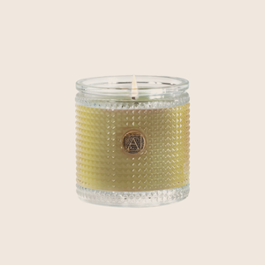 Tangy citrus notes blended with cassis and peach, accented with rose and musk, make the Grapefruit Fandango Textured Glass Candle a bright and cheery addition to any space. Our candles are all hand-poured in Arkansas. Made with a proprietary wax blend, ethically sourced containers and cotton wicks. Light one of these aromatic candles and transport yourself to a memory or emotion.