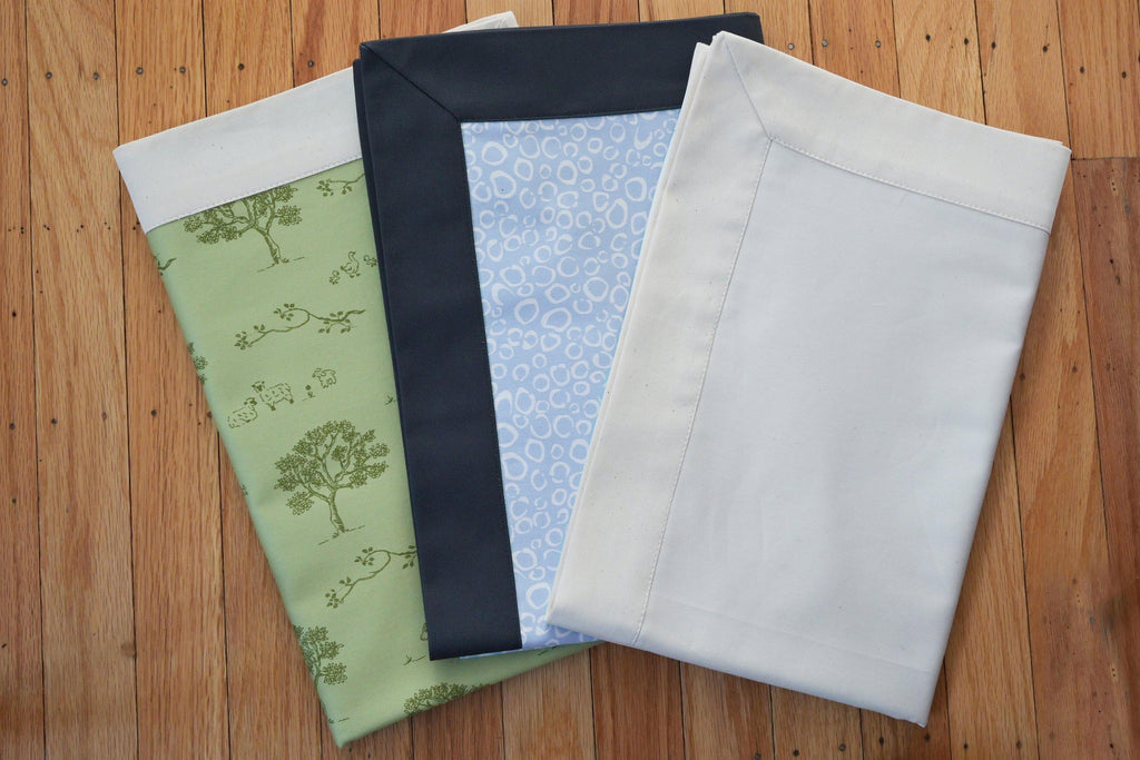 dog bed coverlet fabric samples in green tree pattern, blue with navy trim, and white