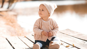 Baby sitting up outside wearing a light pink sweater and hat.