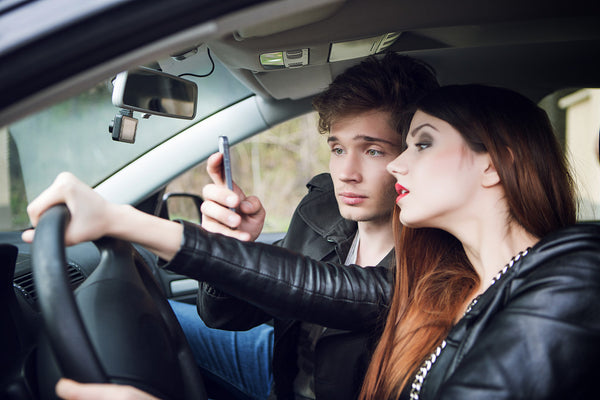 a picture of two teen distracted driving with their phone