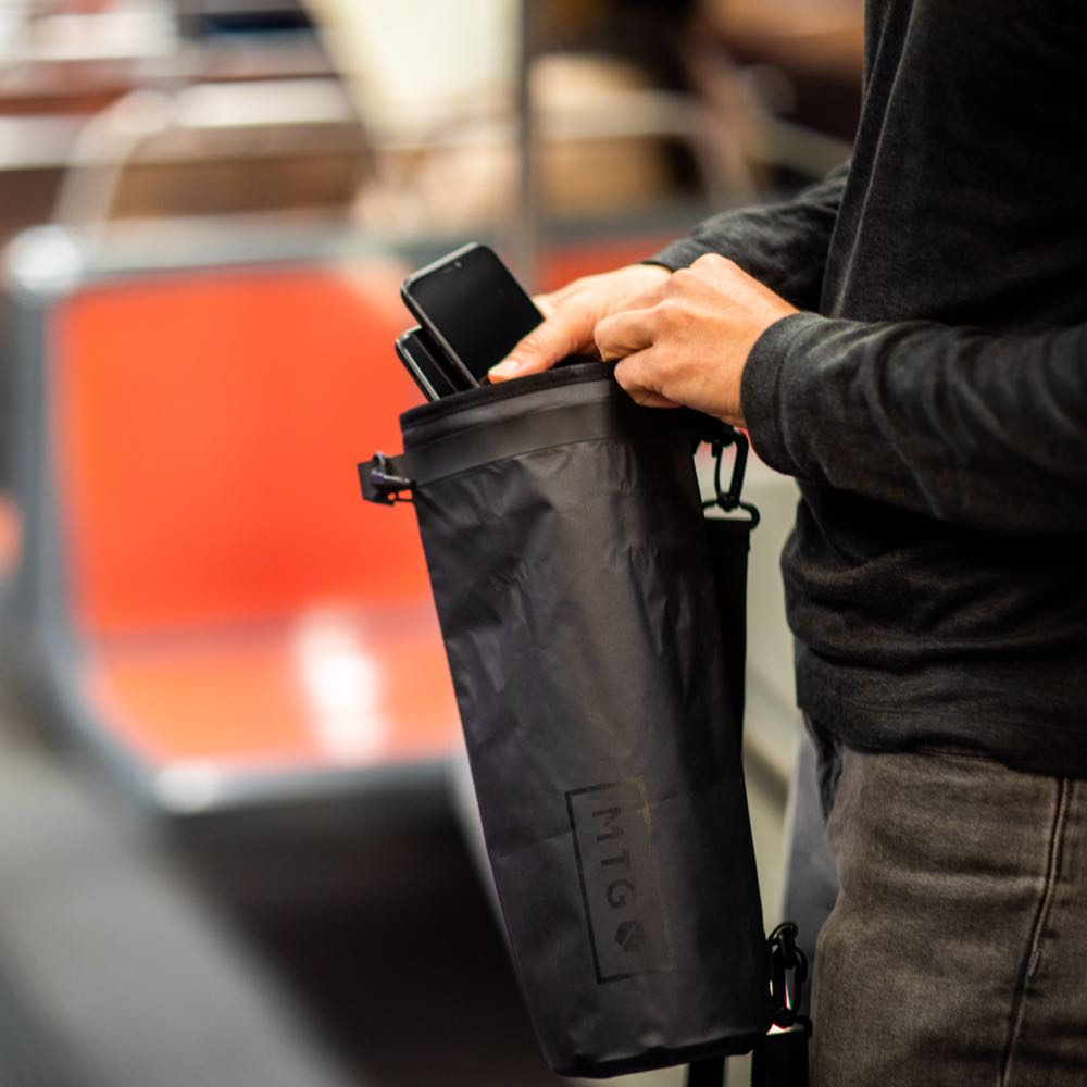 silent pocket signal blocking faraday dry bag with two phones in subway