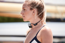 Load image into Gallery viewer, Aftershokz aeropex cosmic black headphones on woman in activewear, aftershokz aeropex headphones, aftershokz headphones, aftershokz wireless headphones, aftershokz aeropex wireless headphones, cosmic black aftershokz headphones, aftershokz headphones black, aftershokz black headphones