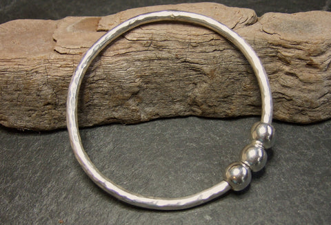 Sterling silver bangle with three moving spheres.