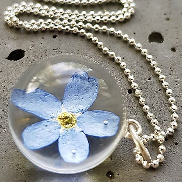 Resin sterling silver necklace with forget me not flowers.