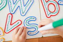 Load image into Gallery viewer, Learn and Grow Write and wipe lowercase letters on desk being traced by a child with a whiteboard marker