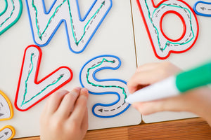 Learn and Grow Write and wipe lowercase letters on desk being traced by a child with a whiteboard marker