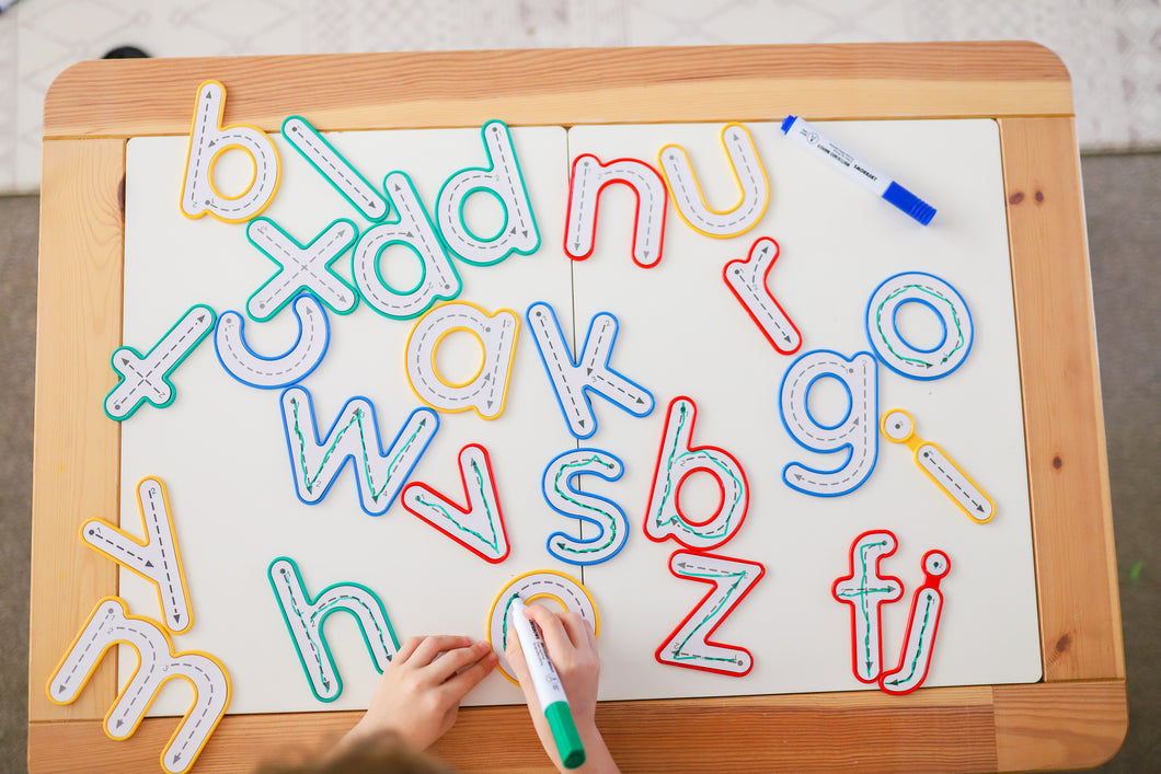 Learn and Grow Write and wipe lowercase letters on board being traced by a child with a whiteboard marker