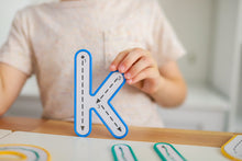 Load image into Gallery viewer, Letter K being held up by child from Learn and Grow Write and wipe lowercase letters