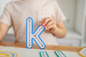 Letter K being held up by child from Learn and Grow Write and wipe lowercase letters