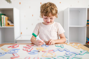 Child using Learn and Grow Write and wipe lowercase letters with a whiteboard marker